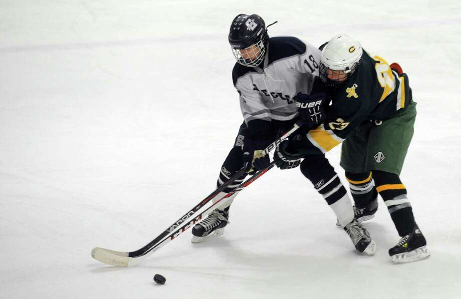 Staples/Weston/Shelton's Evan Mancini and Trinity Catholic's Matt Carlson battle for the puck Wednesday, Feb. 26, 2014, during their ice hockey game at Milford Ice Pavilion in Milford, Conn. Photo: Autumn Driscoll / Connecticut Post