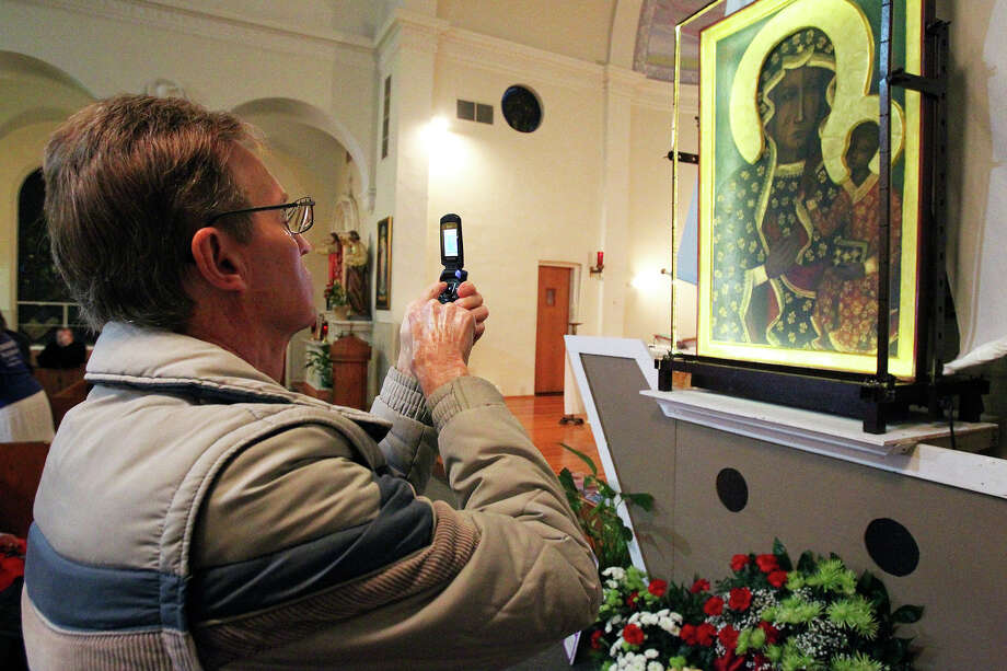 "Glen Jones pictures the icon, Our Lady of Czestochowa, as the ""Polish Madanna"" is displayed at Our Lady Of Sorrows Catholic Church on February 26, 2014. The icon travels around the world to promote the culture of life and family. Photo: TOM REEL"