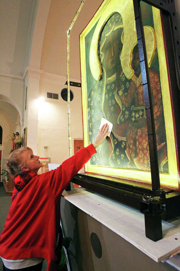 """Charlotte Jones holds a photo of her granddaughter up to Our Lady of Czestochowa, the """"Polish Madanna"""" as it is displayed at Our Lady Of Sorrows Catholic Church on February 26, 2014. Jones was praying for her family member in the chapel.  The icon travels around the world to promote the culture of life and family. Photo: TOM REEL"""