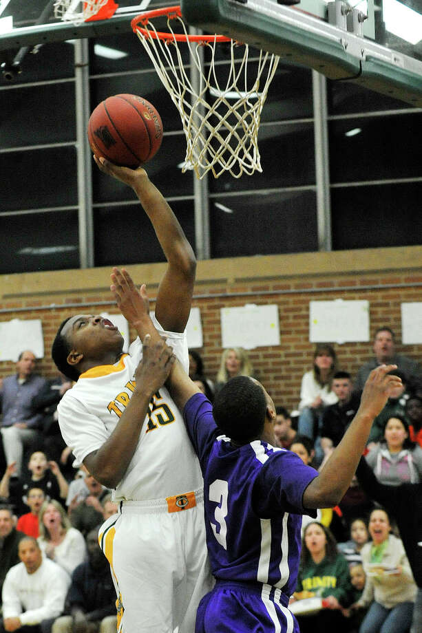 Trinity Catholic's Tyrell St. John puts up a shot while under pressure from Westhill's CJ Donaldson during their game at Trinity Catholic High School in Stamford, Conn., on Wednesday, Feb. 26, 2014. Westhill won, 67-63. Photo: Jason Rearick / Stamford Advocate