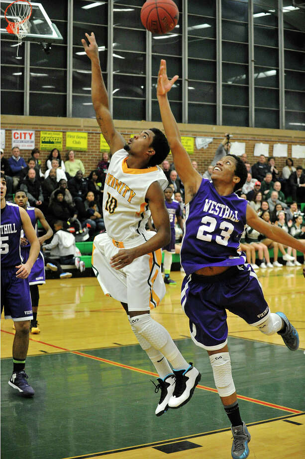 Trinity Catholic's Neno Merritt and Westhill's Juan De La Cruz compete for the rebound during their game at Trinity Catholic High School in Stamford, Conn., on Wednesday, Feb. 26, 2014. Westhill won, 67-63. Photo: Jason Rearick / Stamford Advocate