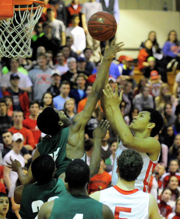 Bassick's Keante Smith, left, stops a layup attempt by Greenwich's C.J. Byrd, during boys basketball action in Greenwich, Conn. on Wednesday February 26, 2014. Photo: Christian Abraham / Connecticut Post