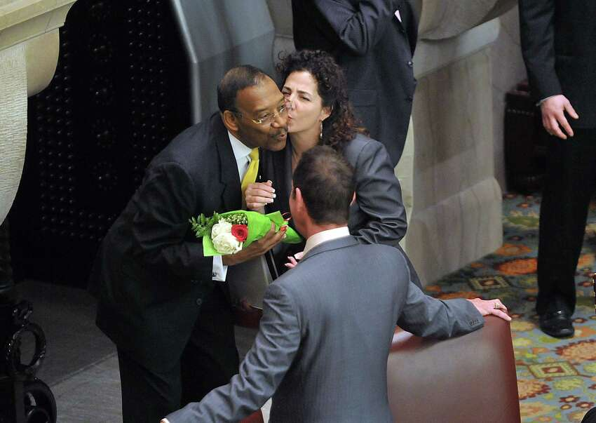Senator Ruben Diaz, left, accepts a kiss on the cheek from Senator Diane Savino after she presented him with flowers on the floor of the Senate Chambers on Wednesday, Feb. 26, 2014, at the Senate Chamber in Albany, N.Y. Senator Jeff Klein, center, looks on. (Paul Buckowski / Times Union)