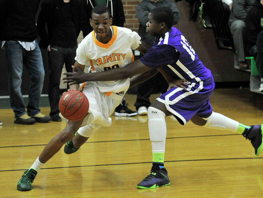 Trinity Catholic's Aaron Wheeler drives to the basket while under pressure from Westhill's Tyrell Alexander during their game at Trinity Catholic High School in Stamford, Conn., on Wednesday, Feb. 26, 2014. Westhill won, 67-63. Photo: Jason Rearick / Stamford Advocate