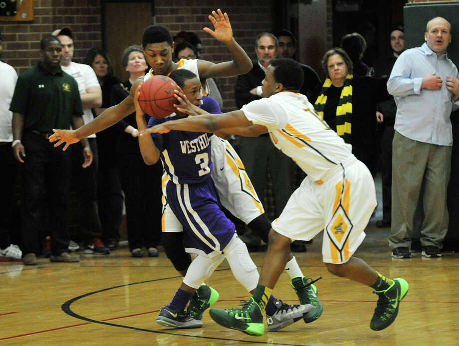 Westhill's CJ Donaldson is double-teamed by Trinity Catholic's Tremaine Fraiser, background, and Tyrell St. John during their game at Trinity Catholic High School in Stamford, Conn., on Wednesday, Feb. 26, 2014. Westhill won, 67-63. Photo: Jason Rearick / Stamford Advocate