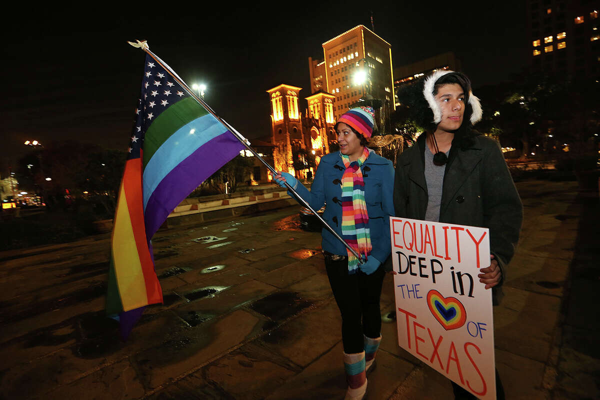 Minda Tovar, left, and her son, Gavyn Rodriguez along with other supporters of same sex marriage gather in front of the Bexar County Courthouse to celebrate a preliminary injunction granted by U.S. Federal Judge Orlando Garcia declaring the ban unconstitutional earlier in the day on Wednesday, Feb. 26, 2014.