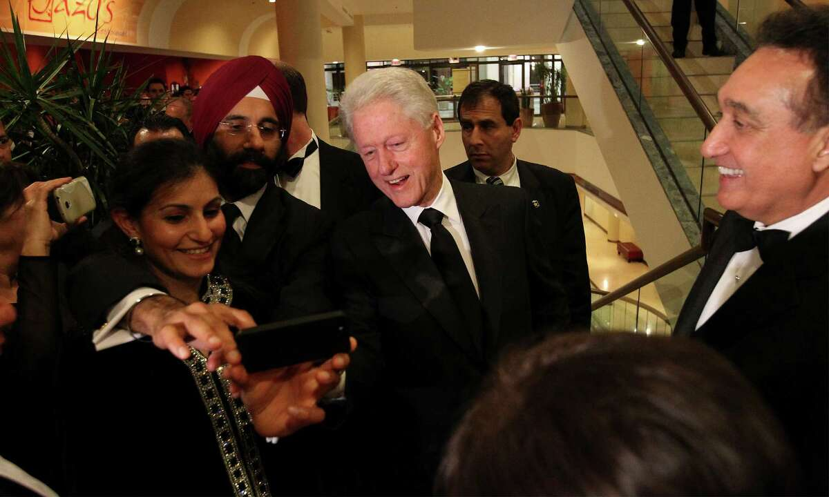 Former President Bill Clinton (center) joins with guests for a
