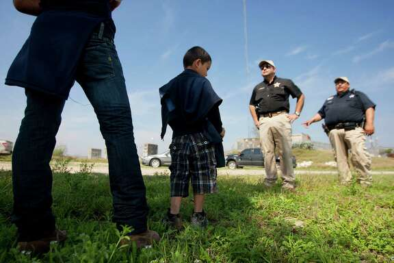 "Hidalgo County Precinct 3 Constable Lazaro Gallardo, Jr., and a deputy talk with a 4-year-old boy and his 17-year-old uncle from Honduras who approached Gallardo in Anzaldulas Park after crossing the Rio Grande from Mexico in Mission. Anzaldulas Park is on the frontline of what federal officials have dubbed ""the surge,"" a steep increase in the numbers of children caught crossing the border illegally and alone. Arrests have spiked from 8,000 in 2008 to more than 38,000 last year."