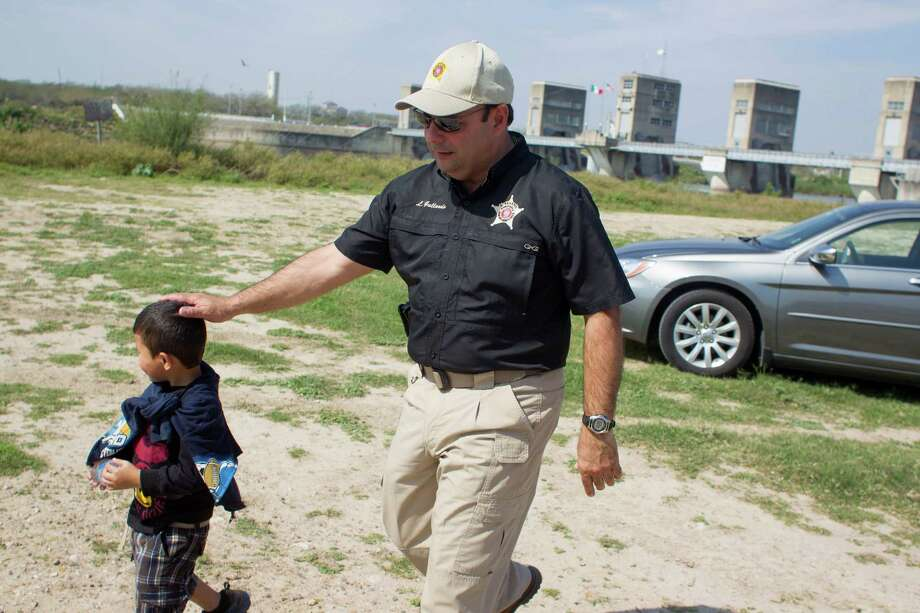 Waiting for Border Patrol, Hidalgo County Precinct 3 Constable Lazaro Gallardo, Jr., walks with a 4-year-old boy from Honduras who crossed from Mexico into Anzaldulas Park with his 17-year-old uncle. Photo: Johnny Hanson, Houston Chronicle / © 2014  Houston Chronicle