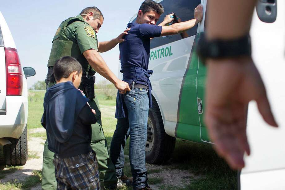Boarder Patrol agents escort a 4-year-old boy and his 17-year-old uncle into a transport vehicle after the two crossed the Rio Grande from Mexico into Anzaldulas Park and turned themselves into a Hidalgo County Precinct 3 Constable. Photo: Johnny Hanson, Houston Chronicle / © 2014  Houston Chronicle