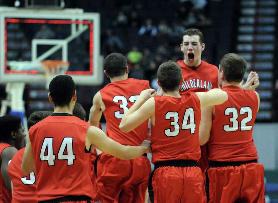 Guilderland's Marc DuMoulin, right, is joined by teammates on the floor after defeating Columbia after five overtime in their  Class AA boys' basketball semifinal at the Times Union Center on Wednesday Feb. 26, 2014 in Albany, N.Y. (Michael P. Farrell/Times Union) Photo: Michael P. Farrell / 00025909A