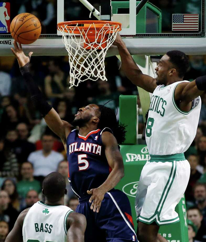 Atlanta Hawks forward DeMarre Carroll (5) shoots a reverse layup against Boston Celtics forwards Jeff Green (8) and Brandon Bass (30) during the first quarter of an NBA basketball game in Boston, Wednesday, Feb. 26, 2014. (AP Photo/Elise Amendola) ORG XMIT: MAEA102 Photo: Elise Amendola / AP
