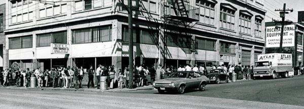 Here's the old REI building on 11th Avenue in Capitol Hill in April 1973, with people lining up for the store's spring camping sale. REI was founded in Seattle in 1938.