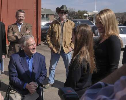 In this Feb. 18, 2014 file photo Texas gubernatorial candidate Greg Abbott, left, visits with supporters during a stop in Denton, Texas, to promote early voting with Rocker Ted Nugent, wearing cowboy hat, center. (AP Photo/The Dallas Morning News, Ron Baselice) Photo: Ron Baselice, Associated Press