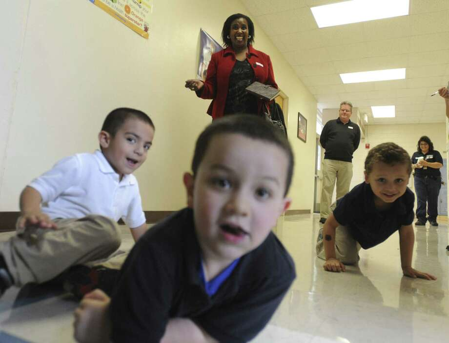 Dr. Mantsose Jane Sethusha, a lecturer in the College of Education: Department of Early Childhood Education at the University of South Africa, watches children crawl at the Carroll Early Child Education Center. Photo: Billy Calzada / San Antonio Express-News / San Antonio Express-News