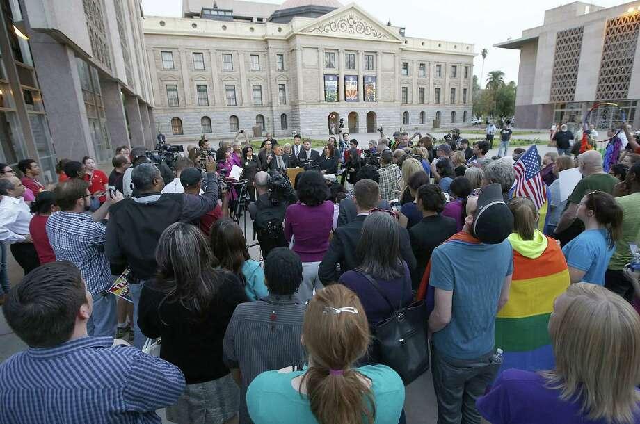 Gay-rights supporters listen as state Sen. Steve Gallardo, D-Phoenix, speaks about Arizona Gov. Jan Brewer's veto. Photo: Ross D. Franklin / Associated Press / AP