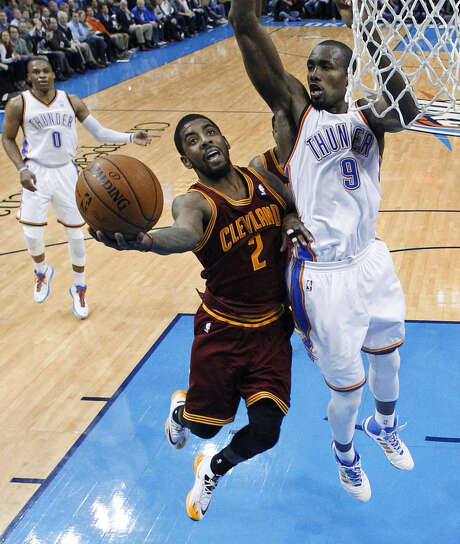 The Cavs' Kyrie Irving is defended by the Thunder's Serge Ibaka on a layup attempt during Cleveland's victory in Oklahoma City. Irving scored 31 points. Photo: Sue Ogrocki / Associated Press / AP