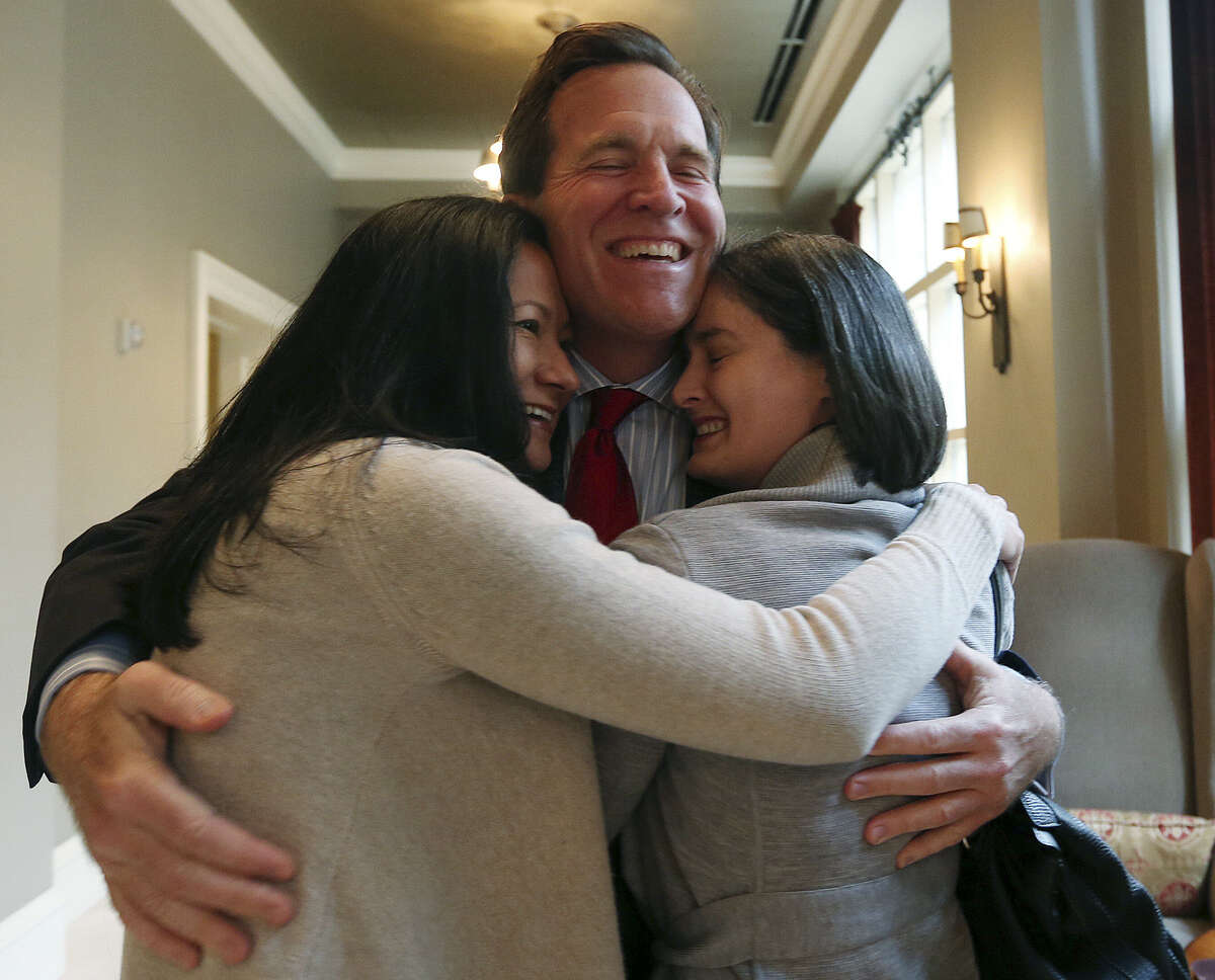 Cleo De Leon (left) and Nicole Dimetman hug attorney Neel Lane in the wake of the ruling. The women were among those who'd sued over the state's ban.