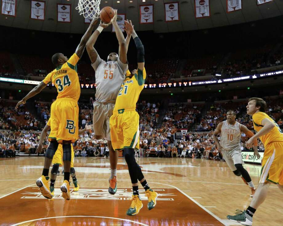 Texas' Cameron Ridley, who had 20 points and 10 rebounds, powers his way between Baylor's Cory Jefferson (34) and Isaiah Austin. Photo: Eric Gay, STF / AP