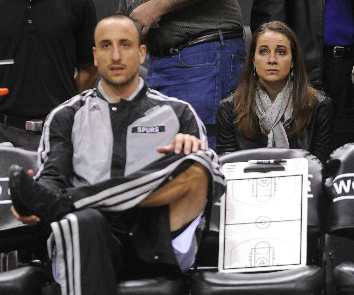 Becky Hammon, who has played for years in the WNBA, sits behind the bench by Spurs player Manu Ginobili at the AT&T Center on Wednesday, Feb. 26, 2014.