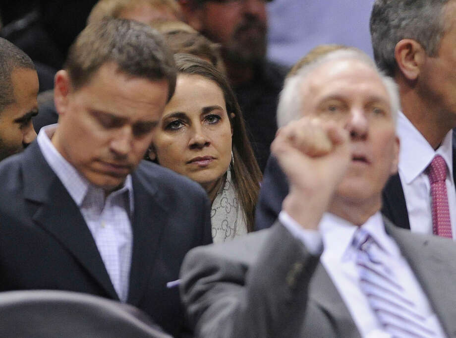 WNBA veteran Becky Hammon sits behind Spurs coach Greg Popovich as the team warms up for their game against the Detroit Pistons in the AT&T Center on Wednesday, Feb. 26, 2014. Photo: Billy Calzada, San Antonio Express-News / San Antonio Express-News
