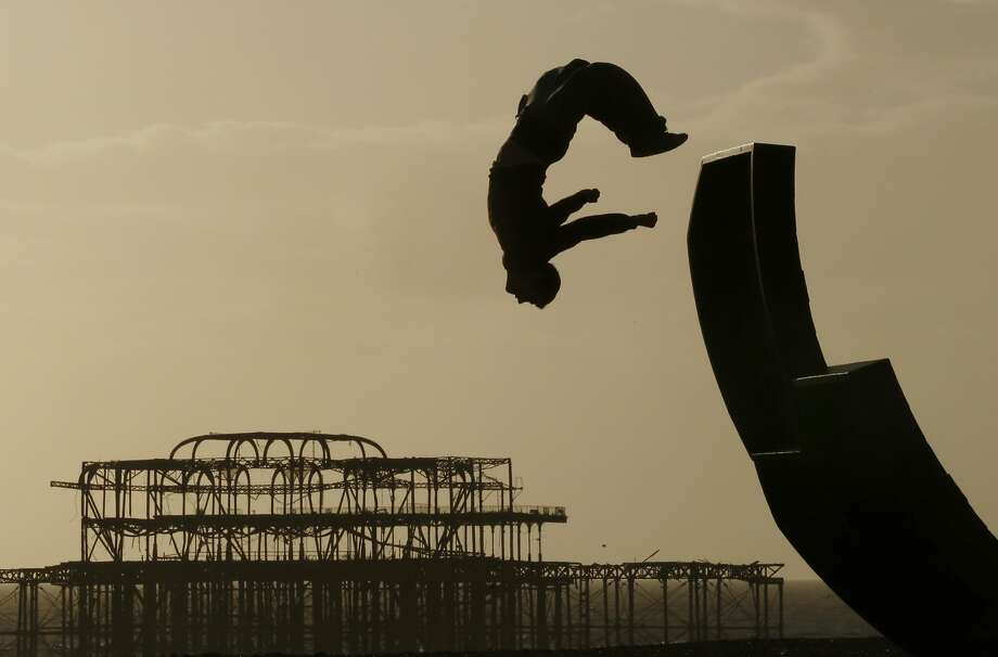 A man somersaults off a sculpture on the beach in front of the old West Pier in Brighton February 26, 2014.  REUTERS/Luke MacGregor  (BRITAIN - Tags: SOCIETY TRAVEL TPX IMAGES OF THE DAY) Photo: Luke Macgregor, Reuters