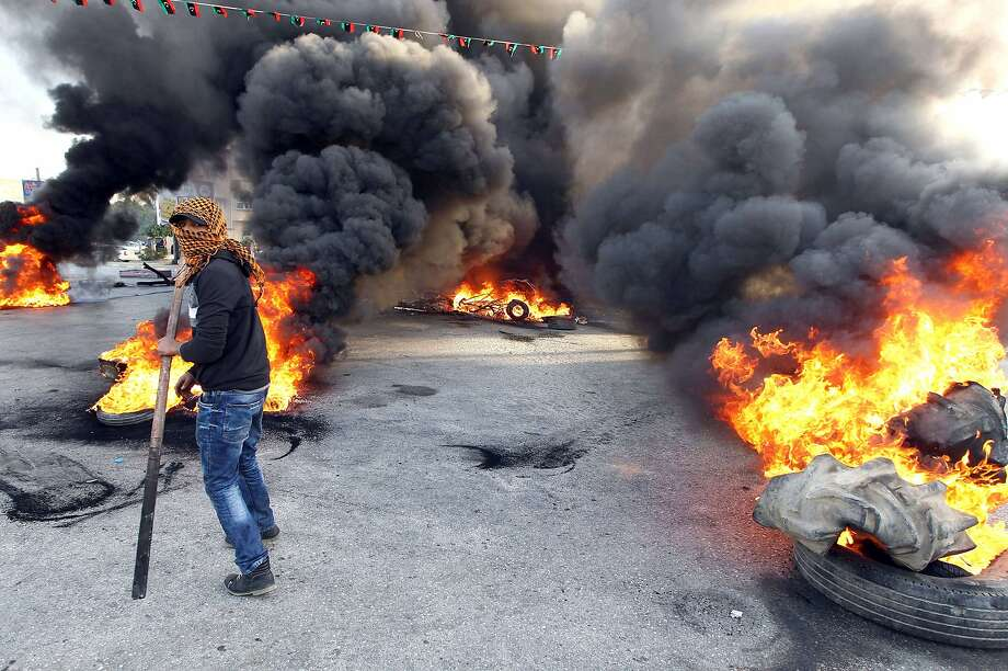 Burning tires block a street in Libya's second largest city, Benghazi, after the deaths 