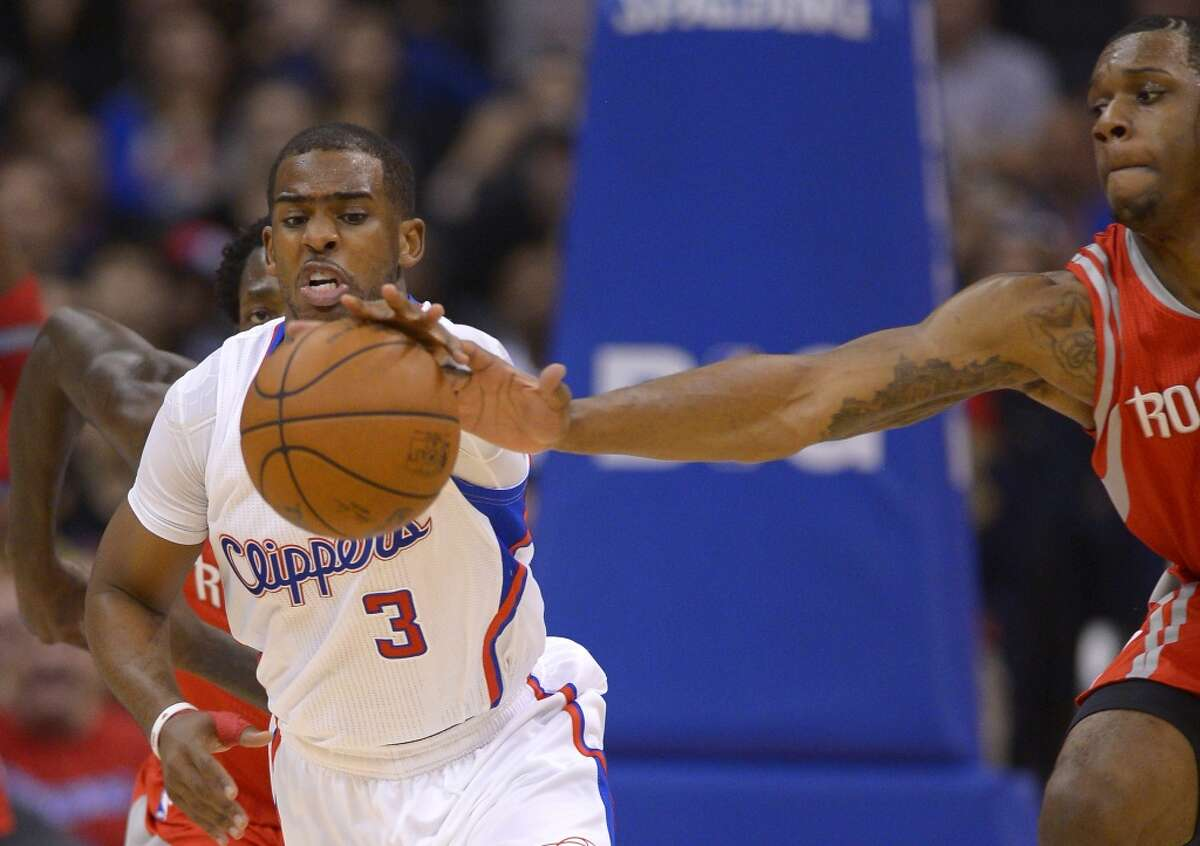 Clippers guard Chris Paul, left, reaches for a loose ball along with Rockets forward Terrence Jones.