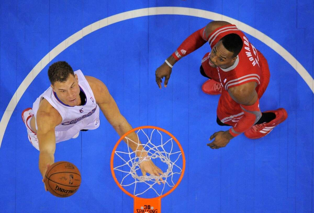 Clippers forward Blake Griffin, left, puts up a shot as Rockets center Dwight Howard looks on.