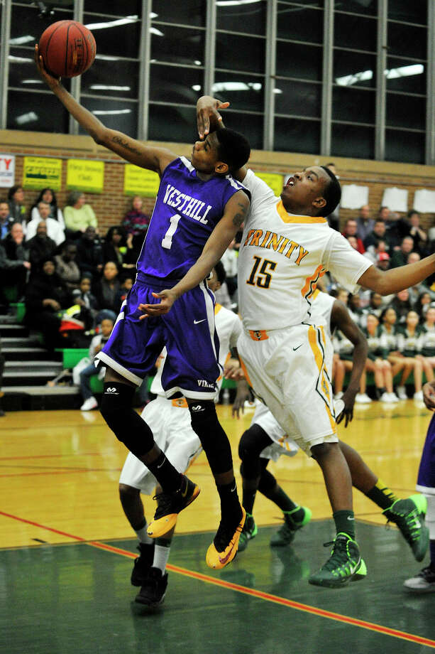 Westhill's Jeremiah Livingston attempts to lay the ball in with Trinity Catholic's Tyrell St. John's hand in his face during their game at Trinity Catholic High School in Stamford, Conn., on Wednesday, Feb. 26, 2014. Westhill won, 67-63. Photo: Jason Rearick / Stamford Advocate