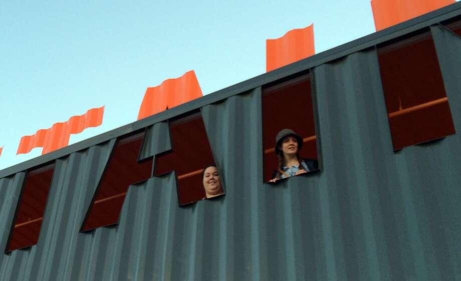 Visitors poke their heads out the letters of the Container Park sign, which is a shipping container itself. Photo: Spud Hilton, Bad Latitude