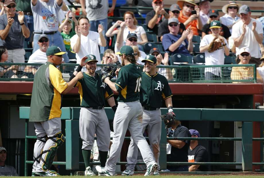 A's Josh Reddick, (16) is congratulated by teammates and fans after his fence climbing catch to rob the Giants' Michael Morse, (38) of a home run in the 2nd inning, as the Oakland Athletics went on to beat the San Francisco Giants 10-5 in a spring training game at Scottsdale Stadium, in Scottsdale, Arizona on Wednesday Feb. 26, 2014. (Michael Macor/The Chronicle) Photo: Michael Macor, The Chronicle