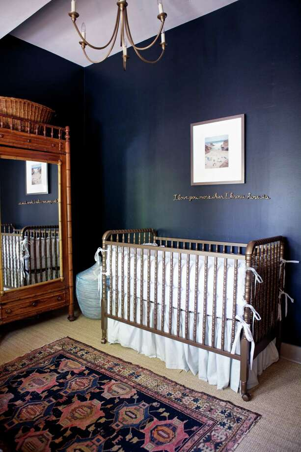 Farrow & Ball's Black Blue shade on the walls in the nursery creates a contrast with the gold-tone cradle and wall art by Tara Conley and Christian Chaize. Photo: Kate LeSueur / ONLINE_YES