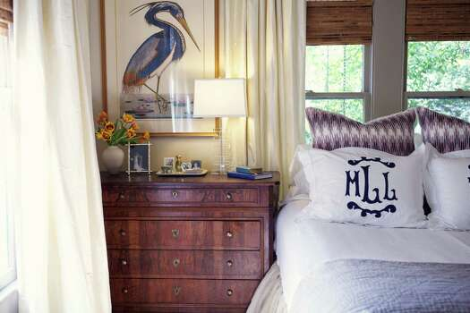 The master bedroom in Meg Lonergan's Heights bungalow features a pair of French antique Louis Philippe chests, topped with a pair of numbered Louisiana heron etchings, which Lonergan declares her best thrift store find of all time. The ottomans were originally midcentury Henredon side tables found at the Guild Shop, cut down and then with a tufted upholstered top added. The French chandelier is from Janet Wiebe Antiques. Photo: Kate LeSueur / ONLINE_YES