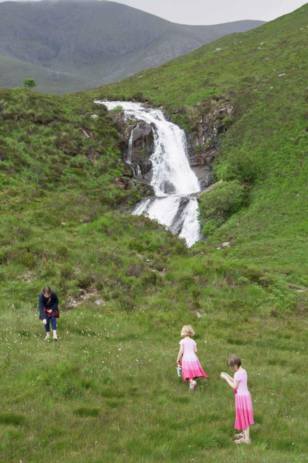Right: Children enjoy a roadside waterfall on the Isle of Skye.