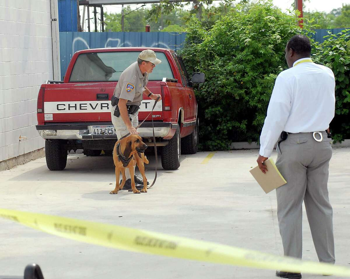 In this file photo, former Fort Bend County Sheriff's Deputy Keith Pikett brings a blood hound to the 6000 block of Wallisville Road to detect the scent of a suspect who left a vehicle behind a bar after assaulting a police officer on Aug. 26, 2009. At right is detective Steven Straughter.