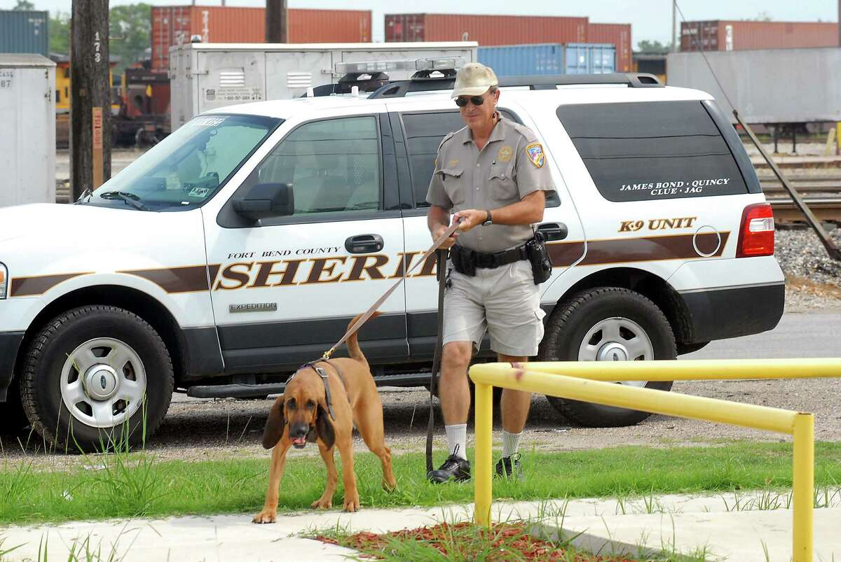 Deputy Keith Pikett and a blood hound search for a suspect's scent on Wallisville Road, Aug. 26, 2009. File photo.