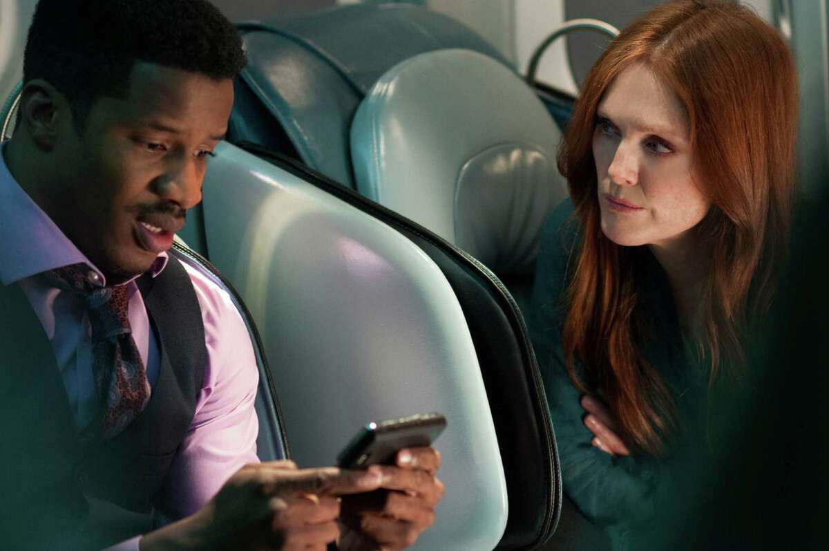 """This image released by Universal Pictures shows Nate Parker, left, and Julianne Moore in a scene from """"Non-Stop."""" (AP Photo/Universal Pictures, Myles Aronowitz)"""