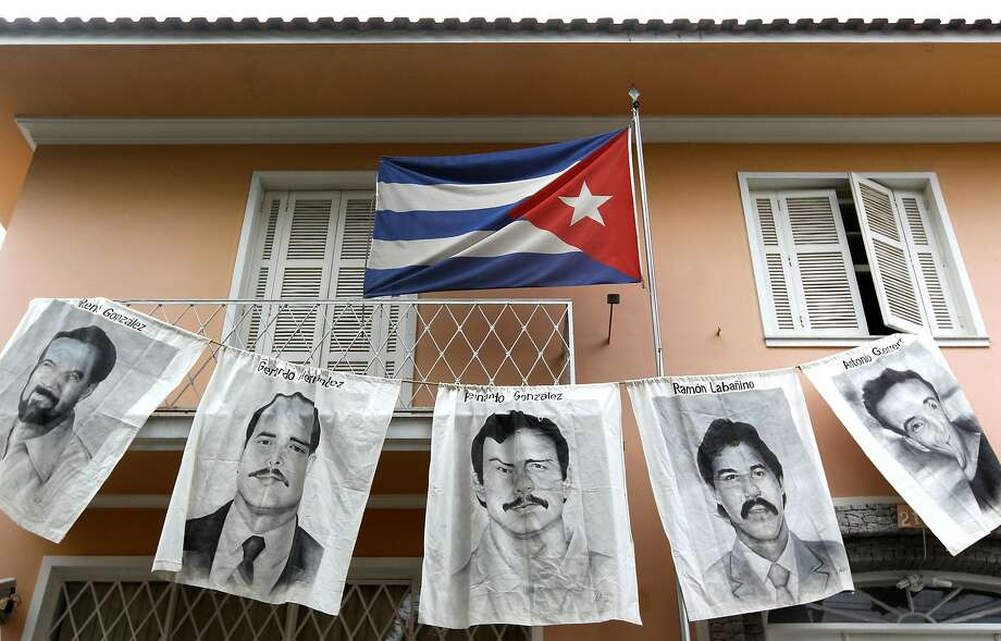 "(FILES)Posters with portraits of five Cubans jailed in the United States - Rene Gonzalez Sehwerert, Gerardo Hernandez Nordelo, Fernando Gonzalez Llort(C), Ramon Labanino Salazar and Antonio Guerrero Rodriguez - are dispayed in this April 7, 2010 file photo in front of Cuba's Consulate in Sao Pablo, Brazil.  One of the so-called ""Cuban Five"" -- intelligence agents convicted in a 2001 US spy case that made them heroes in Havana -has been told he will be released from prison, his lawyer told a Miami newspaper on January 29, 2014. Fernando Gonzalez, who is serving a 17-year prison sentence for not registering as a foreign agent and possessing false identity papers, would be the second  member of the group to be released. His lawyer Ira Kurzban told El Nuevo Herald newspaper that the Bureau of Federal Prisons had set Fernandez's release for February 27 for good conduct. Fernandez was arrested in 1998 along with four other Cuban intelligence agents for infiltrating the Key West Naval Air Station and Cuban exile groups in Miami.AFP PHOTO / Nelson ALMEIDANELSON ALMEIDA/AFP/Getty Images Photo: Nelson Almeida, AFP/Getty Images"
