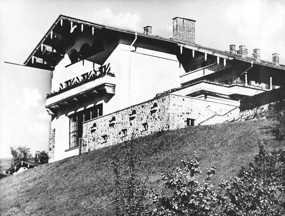 "Hitler's famous ""Berghof"" (mountain house) near Berchtesgaden was perched on a 3,000 Feet high mountainside, it overlooked a lovely valley. Its approaches, along steep winding roads, were guarded by SS Troops. Here the Nazi ""Fuehrer"" used to week-end with Eva Braun and entertain envoys from countries he plotted to conquer. The luxuriously appointed house contained a huge reception room, equipped with a movie screen and a window 26 Feet wide, from which to enjoy the mountain scenery. Air raid shelters tunneled deep into the mountainside were furnished as living quarters in case of attack. But Hitler wasn't there when the planes finally came."