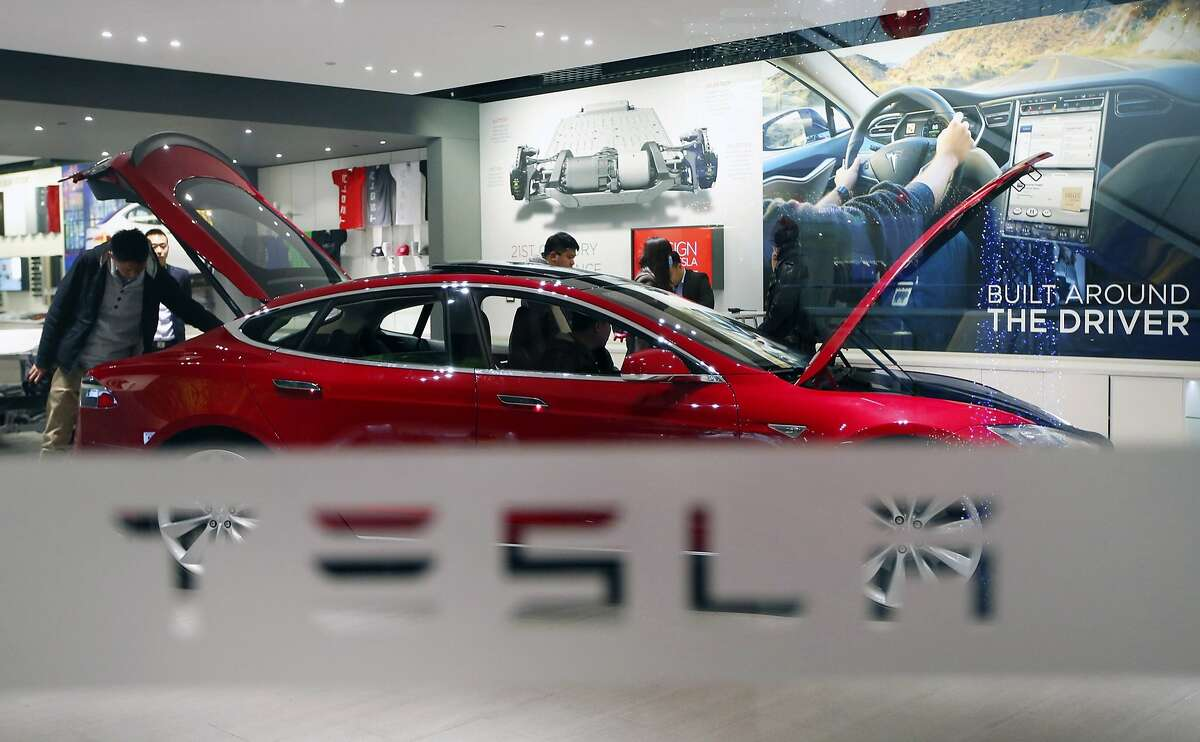 A man looks around Tesla Motors' Model S P85 at its showroom in Beijing in this January 29, 2014 file photo. Panasonic Corp is considering investing in a U.S. car battery plant planned by Tesla Motors Inc, sources familiar with the plan said on February 26, 2014, with total investment estimated by one source around 100 billion yen ($979 million). REUTERS/Kim Kyung-Hoon/Files (CHINA - Tags: BUSINESS TRANSPORT)