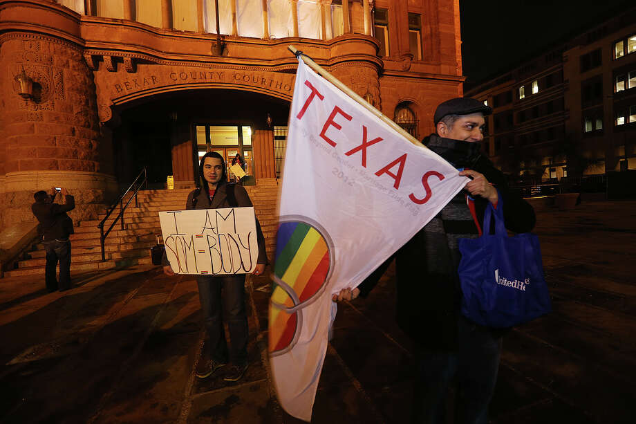 Jorge Estevez, left, and Carlos Soto along with other supporters of same sex marriage gather in front of the Bexar County Courthouse to celebrate a preliminary injunction granted by U.S. Federal Judge Orlando Garcia declaring the ban unconstitutional earlier in the day on Wednesday, Feb. 26, 2014. Two gay couples, Cleopatra De Leon, Nicole Dimetman, Mark Phariss and Vic Holmes filed the federal suit in hopes of overturning the ban. Photo: JERRY LARA, San Antonio Express-News / © 2014 San Antonio Express-News