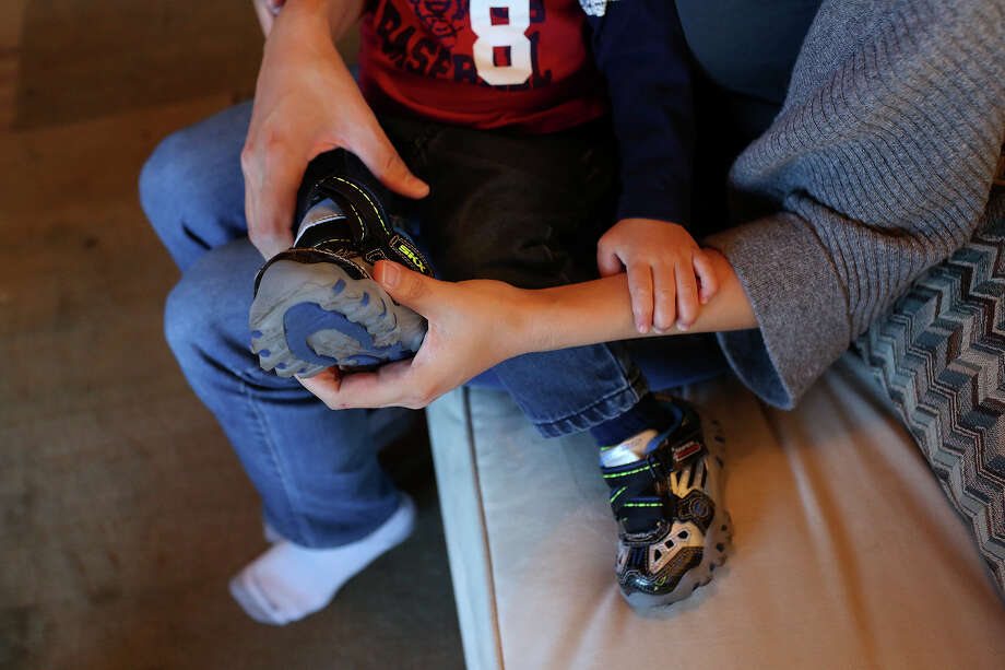 Cleo DeLeon puts on her son's shoes for a trip to the grocery store in Austin on Saturday, Feb. 8, 2014. Photo: Lisa Krantz / San Antonio Express-News