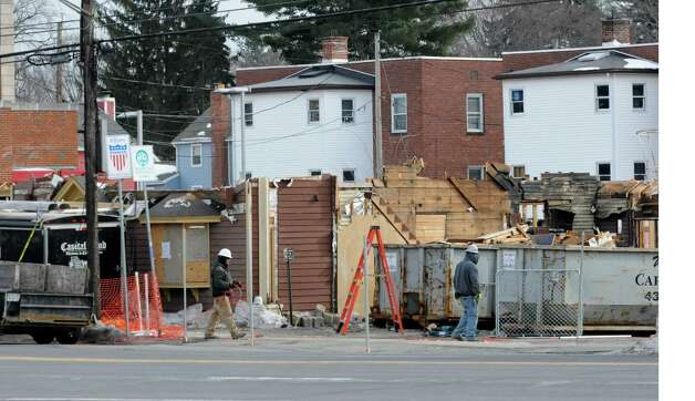 Construction men work on demolishing Sutter's Mining Co. restaurant and bar ,on Western Ave. near UAlbany, to build another eating establishment Thursday, Feb. 27, 2014 in Albany, N.Y.  (Lori Van Buren / Times Union) Photo: Lori Van Buren / 00025939A