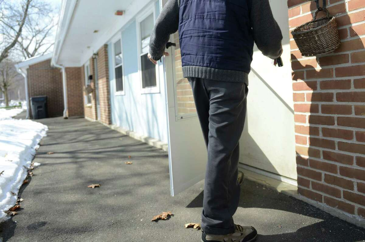 Tenant representative Floyd Banks walks into his home in the Glen Apartments elderly housing complex in Danbury, Conn. Thursday, Feb. 27, 2014. The 100-unit complex on Memorial Drive near Rogers Park is getting $5 million from the state bond commission for needed upgrades and repairs.