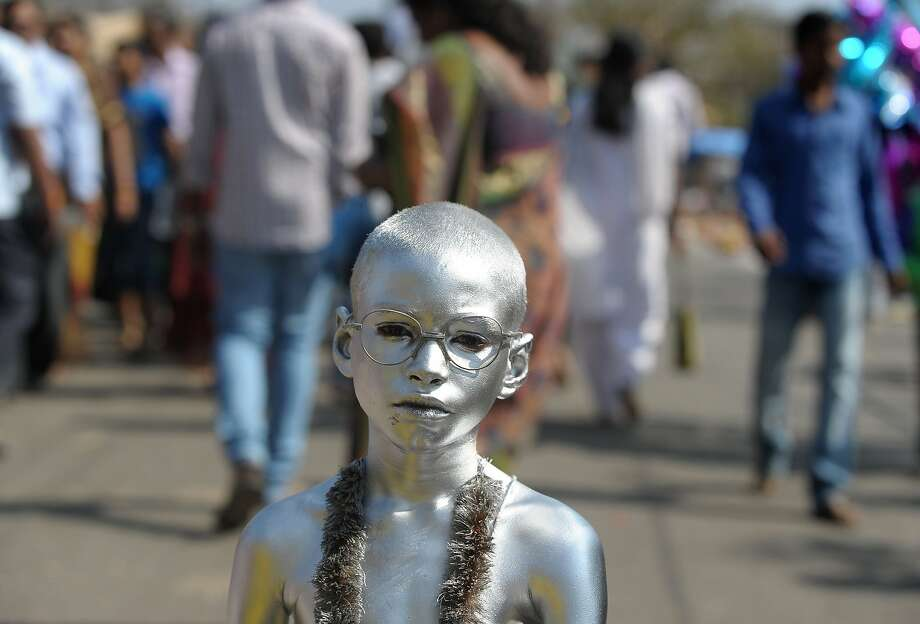 Gandhi glasses:Dressed as a silver Mahatma, a boy begs for alms from Hindu devotees during the 