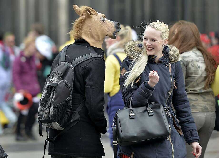 Want to go for a ride? In Cologne, a carnival reveler accosts a pretty blonde with a line straight from the horse's mouth. Photo: Martin Meissner, Associated Press