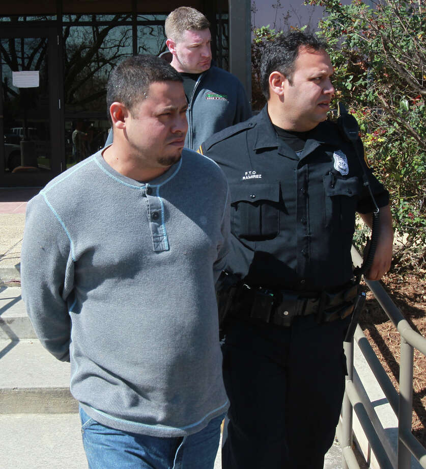 A 38-year-old old robbery suspect (foreground, left) is led to a police car Thursday February 27, 2014. He is one of three suspects apprehended after the trio allagedly took part in the robbery of the Compass Bank at 1014 Goliad Road. The alleged robbers led police on a chase where at one point the car they were in rammed a police car. The names of the suspects have not yet been released. Photo: JOHN DAVENPORT, SAN ANTONIO EXPRESS-NEWS / ©San Antonio Express-News/Photo may be sold to the public