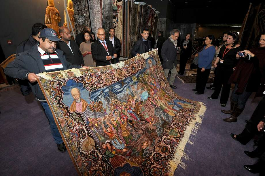 Visitors gather around an Iranian carpet that once belonged to the family of ousted Tunisian dictator Zine El Abidine Ben Ali at an auction in the Tunis suburb in 2012.  The former President's luxury items, once owned by the ousted leader and