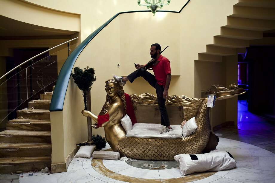 Gaddafi had a particular love of gold. A Libyan Rebel stands and posed on an ornate mermaid loveseat, a wedding gift made to resemble Aisha Gaddafi, daughter of former Libyan dictator Moammar Gaddafi, while guarding Aisha's home from looters in 2011 in Tripoli, Libya. Photo: Benjamin Lowy